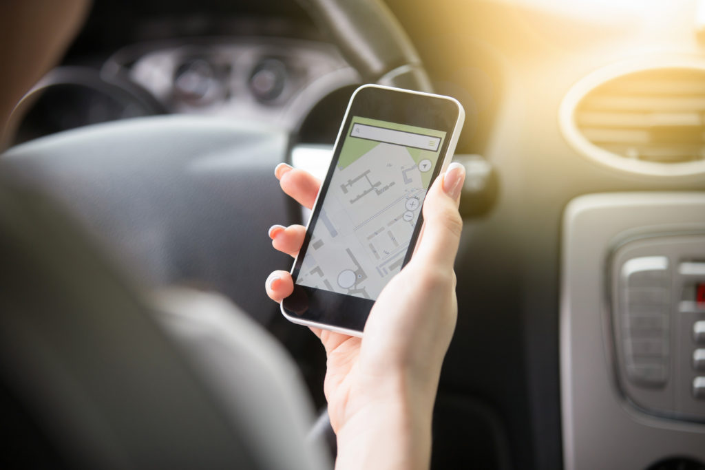 Close up of traveler female hand holding her phone with navigation system. Young woman traveling by car, trying to find the shortest route to a certain destination